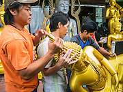 "12 NOVEMBER 2012 - BANGKOK, THAILAND:   Workers deliver a Buddha statue to shop on Bamrung Muang Street in Bangkok. Thanon Bamrung Muang (Thanon is Thai for Road or Street) is Bangkok's ""Street of Many Buddhas."" Like many ancient cities, Bangkok was once a city of artisan's neighborhoods and Bamrung Muang Road, near Bangkok's present day city hall, was once the street where all the country's Buddha statues were made. Now they made in factories on the edge of Bangkok, but Bamrung Muang Road is still where the statues are sold. Once an elephant trail, it was one of the first streets paved in Bangkok. It is the largest center of Buddhist supplies in Thailand. Not just statues but also monk's robes, candles, alms bowls, and pre-configured alms baskets are for sale along both sides of the street.    PHOTO BY JACK KURTZ"