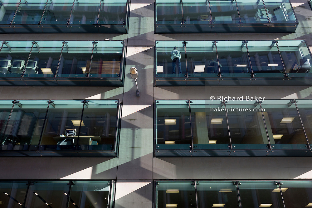 A businessman stands in a warm spot at the window of his company offices, on 13th February 2017, in the City of London, United Kingdom.
