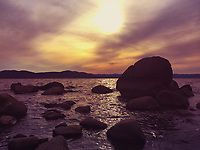 Rocks on river during sunset