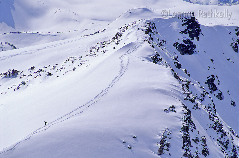 Skier carries skis up Piccolo Mountain, near Whistler, BC, circa 1989-90. This area of the mountain now has a chairlift and is easily accessible, but used to be cherished for fresh powder and good fall lines for skiing.