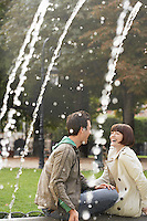 Couple laughing sitting on edge of fountain view past water jets