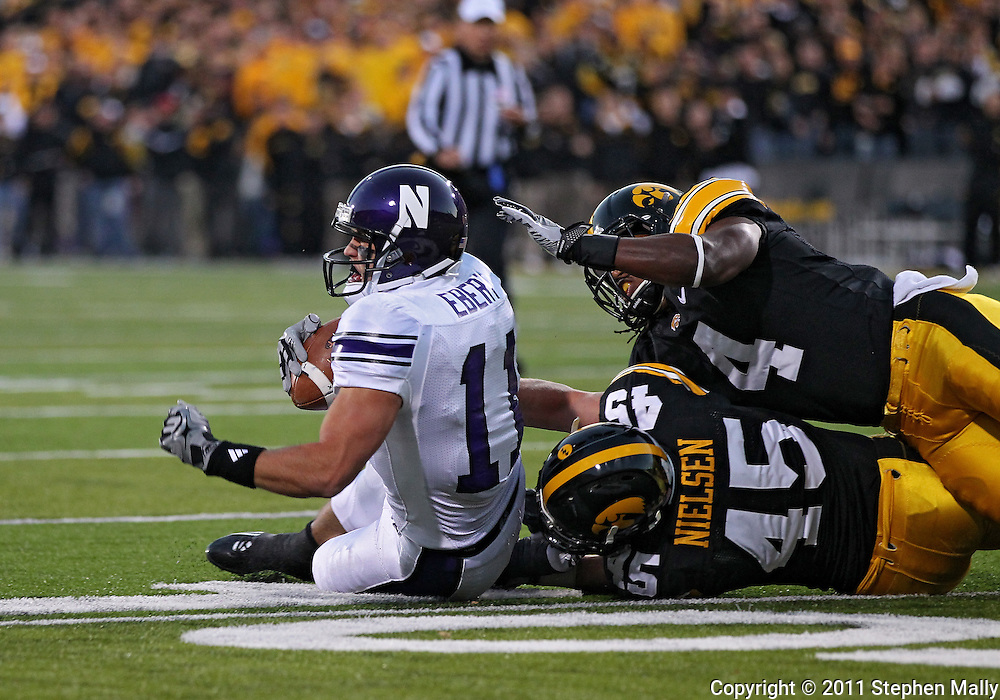 October 15, 2011: Northwestern Wildcats wide receiver Jeremy Ebert (11) is pulled down by Iowa Hawkeyes linebacker Tyler Nielsen (45) and Iowa Hawkeyes defensive back Jordan Bernstine (4) during the first half of the NCAA football game between the Northwestern Wildcats and the Iowa Hawkeyes at Kinnick Stadium in Iowa City, Iowa on Saturday, October 15, 2011. Iowa defeated Northwestern 41-31.