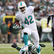 Charles Clay, Miami Dolphins, avoids the tackle of Demario Davis during the New York Jets Vs Miami Dolphins  NFL American Football game at MetLife Stadium, East Rutherford, NJ, USA. 1st December 2013. Photo Tim Clayton