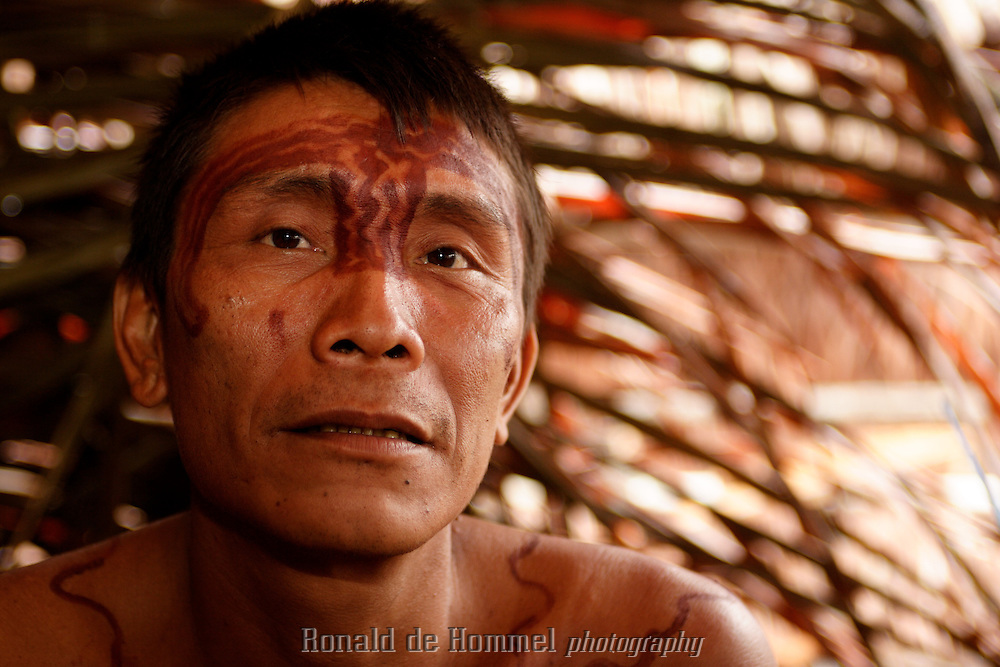 Viriunaveteri, Venezuela. A Yanomami man watching a tribal dance. .The village of Viriunaveteri consists of 15 huts around a muddy square. It's situated in the Venezuelan Amazone several days by boat from the nearest town. This community on the banks of the Casiquiare is one of the few Yanomami villages that actually has some contact with the outside world. Most other tribes live deeper in the jungle.