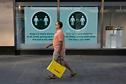 With a further 149 reported dying from Coronavirus in the last 24hrs, taking the UK death toll to 43,320, a shopper carrying a Selfridges bag walks past a screen with social distancing guidelines in the window of Marks & Spencer on Oxford Street during the Covid pandemic, on 25th June 2020, in London, England.