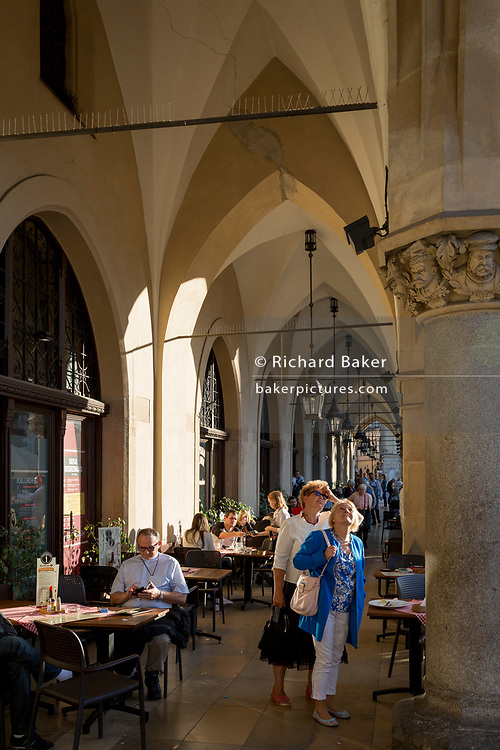 Afternoon sunshine in the arched passageway of the Renaissance Cloth Hall on Rynek Glowny market square, on 22nd September 2019, in Krakow, Malopolska, Poland.