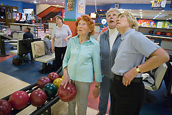 Group of older women looking at score board at ten pin bowling alley,