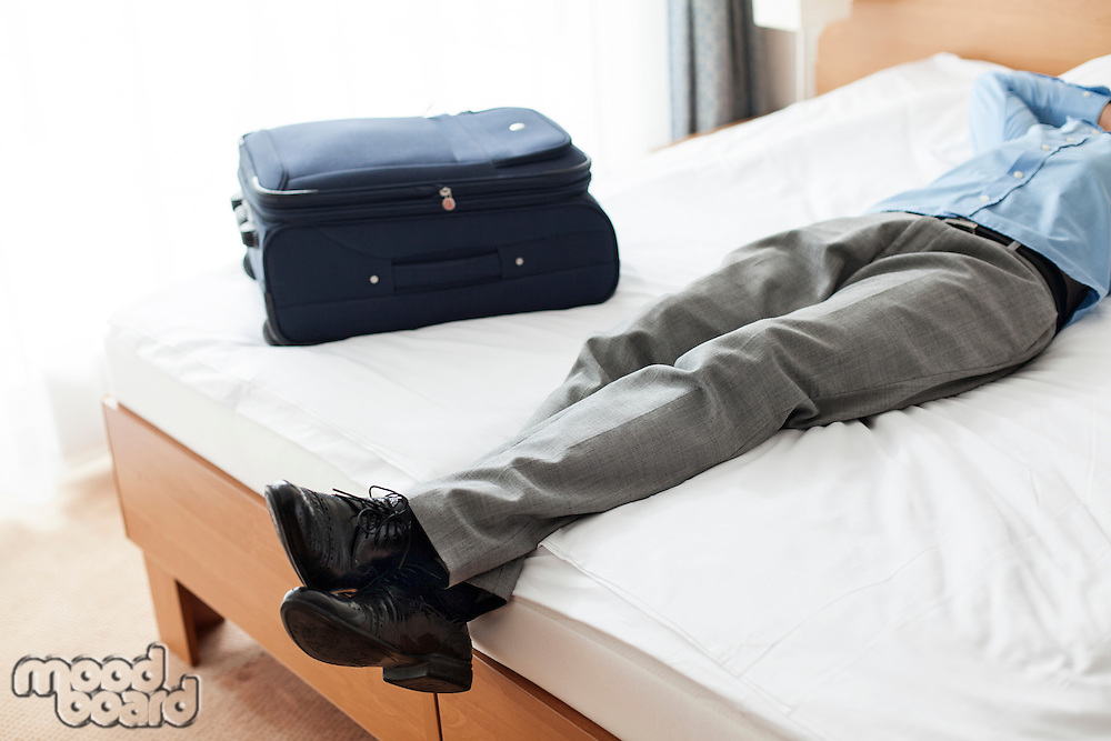 Low section of young businessman sleeping beside suitcase in hotel room