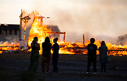 People watch as a 4-alarm fire burns down a large abandoned military barracks located on the north end of the former Mare Island Navy Base August 10, 2014. Crews and equipment from Crocket and Fairfield were on the scene to assist Vallejo firefighters.