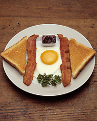 breakfast plate platter one fried egg sunny side up two slices bacon toast grape jelly parsley plate on wooden table top
