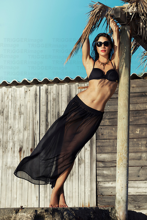 Caucasian female model wearing black swimwear and sunglasses standing outdoors in summer