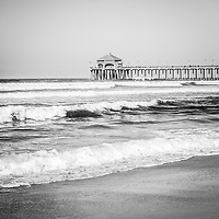 Black and white photo of Huntington Beach Pier. Huntington Beach Pier is a registered historic place in Huntington Beach California. Huntington Beach is a seaside beach city along the Pacific Ocean in Orange County Southern California and is also known as Surf City USA. Image Copyright © Paul Velgos All Rights Reserved.