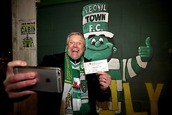 A Yeovil Town fan poses for a selfie with his ticket and the club mascot Jolly Green Giant in the background during the Emirates FA Cup, fourth round match at Huish Park, Yeovil.