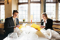Portrait of smiling business couple with menus at restaurant table