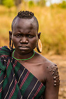 Mursi tribe woman with ear lobe modification to hold clay discs, Omo Valley, Mago National Park, Ethiopia.