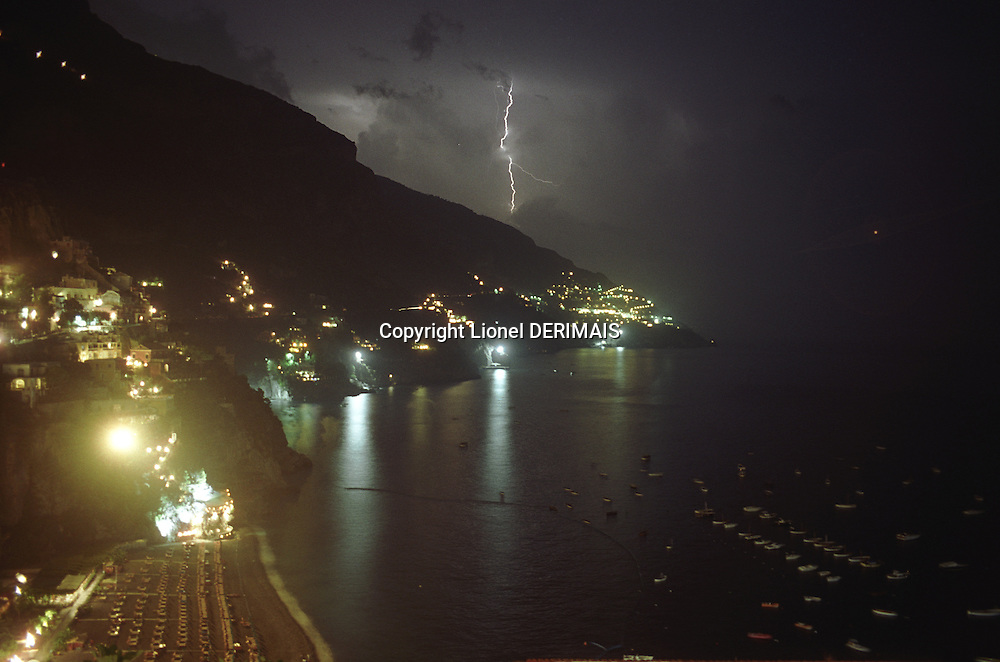 Positano at night with a lightning in the background, Italy.