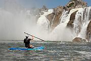 Young boy S.U.P Boarding below the impressive Shoshone Falls, Twin Falls, Idaho.