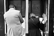 A man and woman making calls at a phone booth in New York City.