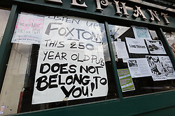 "© Licensed to London News Pictures. 19/06/2015. London, UK. A sign stating ""Listen up Foxtons this 250 year old pub does not belong to you"" in the window of the Elephant and Castle pub in Southwark, south-east London. A group of activists have occupied the Elephant and Castle pub and are squatting in it to prevent Foxtons Estate Agents from opening an Estate Agent branch. The activists, who are against gentrification want the historic pub site to become a community asset with open use. The Elephant and Castle pub closed earlier this year after its license was revoke and in April, representatives of Foxtons notified planning authorities that they intend to open a branch of the estate agents chain in the pub. Photo credit : Vickie Flores/LNP"