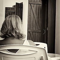 Sun tanned female figure seen from behind sitting on a plastic chair outdoors in summer