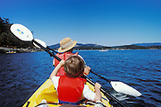 Mother and 5-year old son sea kayaking out of Deer Harbor, Orcas Island, San Juan Islands, Washington.