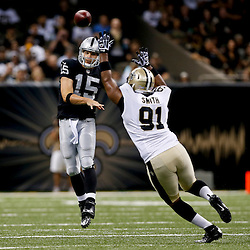 Aug 16, 2013; New Orleans, LA, USA; Oakland Raiders quarterback Matt Flynn (15) throws as New Orleans Saints linebacker Will Smith (91) pressures during the first quarter of a preseason game at the Mercedes-Benz Superdome. Mandatory Credit: Derick E. Hingle-USA TODAY Sports