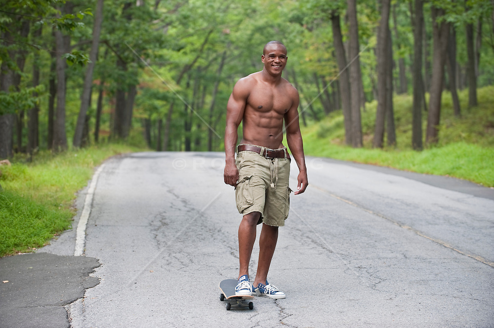 Shirtless goodlooking Afro-American young man on his skateboard in Central Park NYC