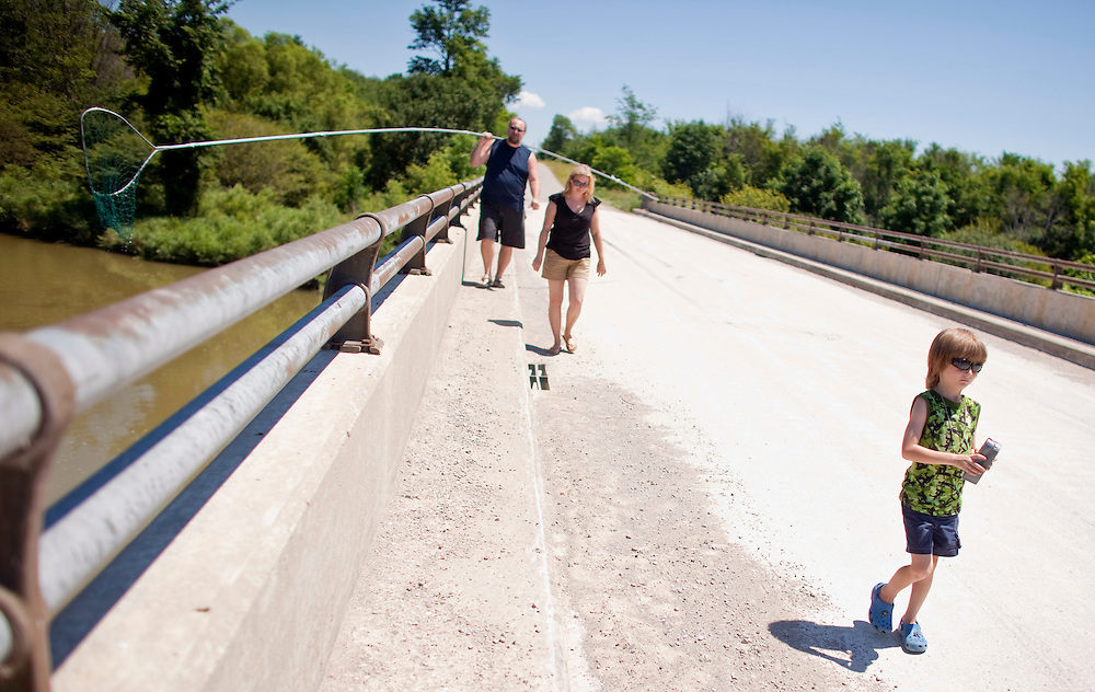 Ailsa Craig, Ontario ---10-07-10---  Shanon, and Teresa Wahl, and their son Ethan, 6, walk along a bridge over the Sauble River as they hunt for turtles to add to the family's collection in preparation for Ailsa Craig, Ontario's Turtle races which take place July 17, 18 in the small Southern Ontario town North of London.<br /> GEOFF ROBINS Toronto Star