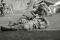 Members of the US 82nd Airborne/505th RCT living History Group take part in the first days battle re-enactment at Fort Paull. A reenactor checks on a &quot;casualty&quot; as the Americans are pushed back <br /> <br />   03 May 2015<br />   Image &copy; Paul David Drabble <br />   www.pauldaviddrabble.co.uk