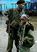 A 9(nine) year old Liberian government gunman is sent back from the firing positions at the 'Old Bridge' in rains during a lull in the battle for the bridges by an elder fighter, Monrovia 28 July 2003. LURD(Liberians United for Reconciliation and Democracy) rebels drove government forces back over the bridge last night leaving the government forces on the Monrovia side of the bridge defending the city.This the Tenth day of continued fighting for the capital despite the call for ceasefire and heavy rains.<br /> EPA PHOTO/NIC BOTHMA