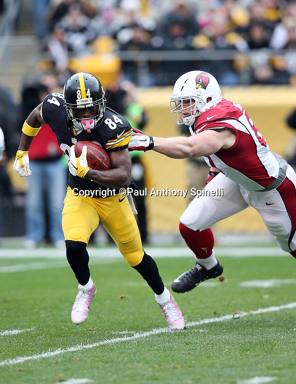Pittsburgh Steelers wide receiver Antonio Brown (84) avoids the outstretched hand of a would be tackler as he returns a first quarter punt during the 2015 NFL week 6 regular season football game against the Arizona Cardinals on Sunday, Oct. 18, 2015 in Pittsburgh. The Steelers won the game 25-13. (©Paul Anthony Spinelli)