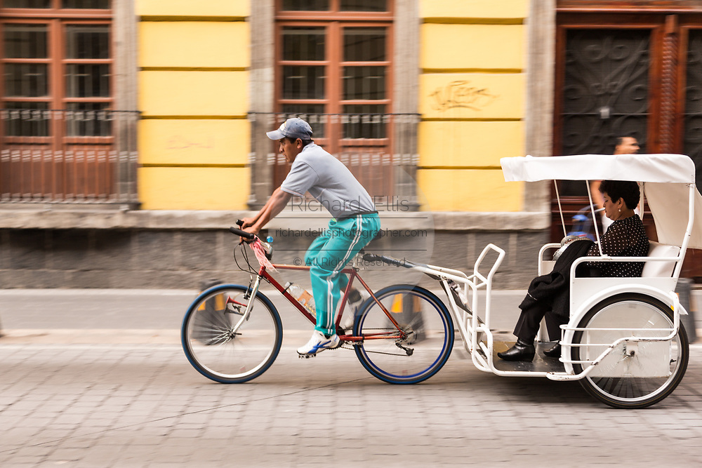 A pedi-cab travels down a street in the historic district of Mexico City, Mexico.