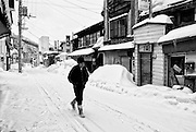 A man walks down the main entertainment district -- now all but deserted -- in Yubari City, on the northernmost island of Hokkaido, Japan. Shuttered up stores are a common sight in the city, which is officially bankrupt.