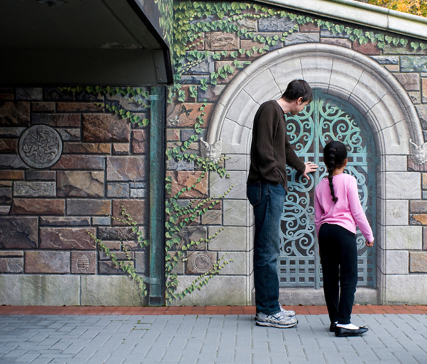 """Frederick, Maryland - Visitors stop to admire the painted door beneath downtown Frederick's tourist attraction, """"the Painted Bridge,"""" a large trompe l'oeil of faux stonework and ivy that graces the concrete bridge that crosses Carroll Creek, the narrow waterway bisecting downtown Frederick.  Photo by Susana Raab"""