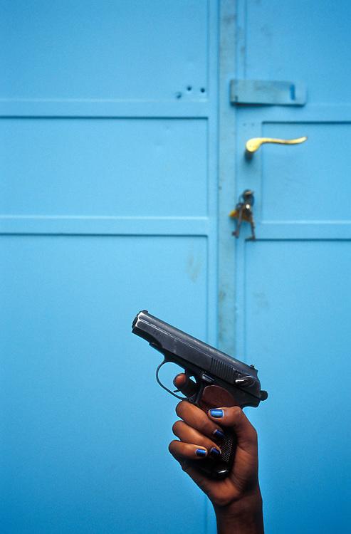 A female Eritrean soldier holds a handgun in front of a blue door in Asmara, Eritrea.