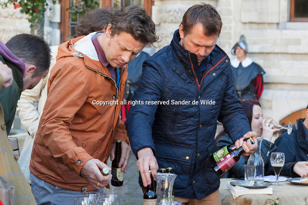 Brussels 2012 10 october. Jamie Oliver(left) and Jimmy Doherty,with bottles British beer on the filmset of a new BBC series called .'Jamie's and Jimmy's.Food Fight Club', where they challenge English products with continental products. This scene is about Belgian Beers, filmed on the main square of Brussels, Grote Markt.