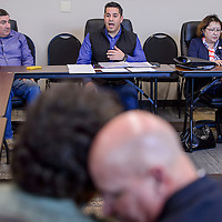 Ben Ray Lujan, center, sits with George Muñoz and Linda Garcia as he conducts a special meeting at the El Morro Event Center in Gallup Friday.