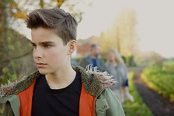 Teenage Boy Walking in Country Road, Parents in Background