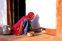 Inde. Rajasthan. Village dans les environs de Barmer. Une femme peint  sa maison pour la fête de nouvel année. (Diwali) // India. Rajasthan. Village near Barmer. Woman painting her house for new year festival (Diwali).