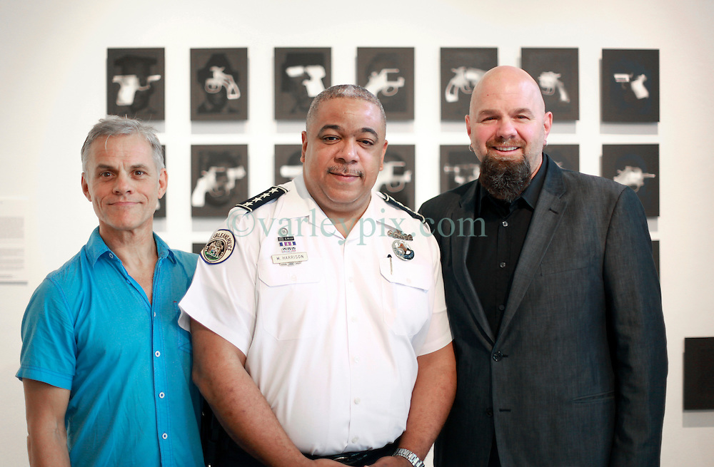 02 October 2014. Jonathan Ferrara Gallery, New Orleans, Louisiana. <br /> R/L; Jonathan Ferrara, 'NOPD police chief Michael S. Harrison and artist Brian Borrello attend the opening of 'Guns In The Hands Of Artists' art show at the Jonathan Ferrara Gallery. The show brings together over 30 internationally acclaimed artists who took parts from 190 destroyed weapons acquired by the New Orleans Police department  and converted them into art.  <br /> Photo; Charlie Varley/varleypix.com