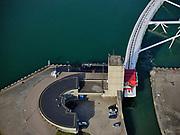 Nederland, Zuid-Holland, Hoek van Holland, 14-09-2019; Nieuwe Waterweg, Haven van Rotterdam. Functioneringssluiting Maeslantkering. De waterkering in de Nieuwe Waterweg wordt een maal per jaar, voordat het stormseizoen begint, getest. Tijdens het sluiten van de kering ligt alle scheepvaartverkeer naar de Rotterdamse haven stil. Details van de constructie, rrn deu en de ingan van het 'dok waar de deur zich normaal gesproken bevindt. De Maeslantkering sluit normaal gesproken alleen bij dreigende stromvloed en bij een waterstand van 3 meter of meer boven NAP. De kering, onderdeel van de Deltawerken, vormt samen met de Hartelkering de Europoortkering en beschermt Rotterdam en achterland bij extreme waterstanden.<br /> Hook of Holland - Port of Rotterdam. Aerial view of the new storm surge barrier (Maeslantkering) in the Nieuwe Waterweg during the so-called functioning closure, taking place one a year before the storm season begins. The waterway, leading to the Port of Rotterdam (at the horizon), is closed during the test. <br /> luchtfoto (toeslag op standard tarieven);<br /> aerial photo (additional fee required);<br /> copyright foto/photo Siebe Swart