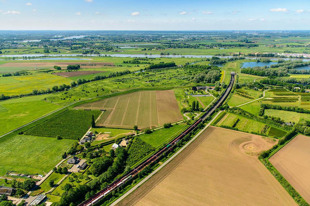 Nederland, Gelderland, Duiven, 29-05-2019; Groessen, natuurgebied Kandia. Betuweroute met vrachttrein, verlaat de tunnel onder het Pannerdensch kanaal. Neder-Rijn in de achtergrond.<br /> Tunnel Betuweroute, freight railway, Pannerdensch channel (Lower Rhine) on the horizon.<br /> luchtfoto (toeslag op standard tarieven);<br /> aerial photo (additional fee required);<br /> copyright foto/photo Siebe Swart