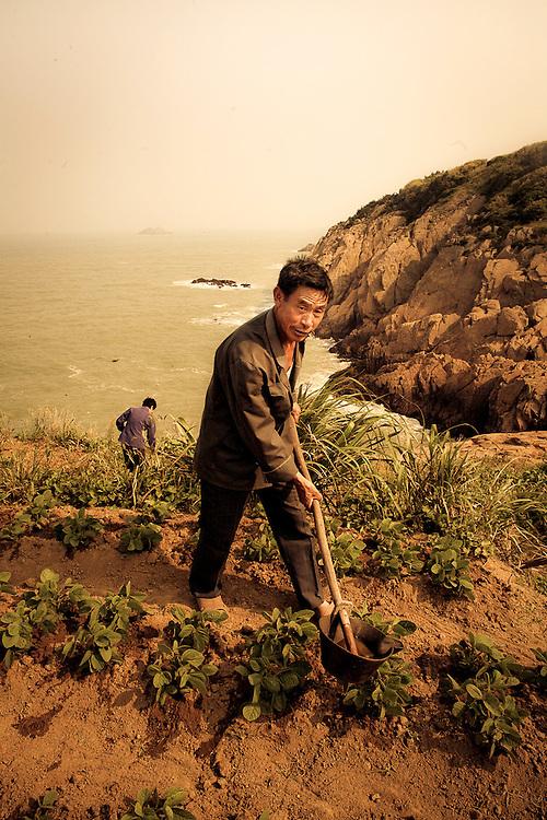 Chinese man tilling farm by ocean