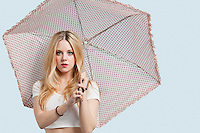 Portrait of young woman holding polka dotted umbrella against light blue background