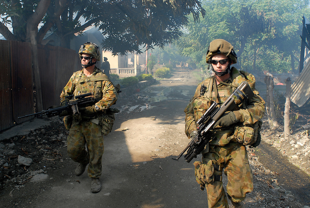 Australian Peacekeepers provide the neceesary security for East Timorese firefighters, the Bombeiros, as they arrive to attempt to put out yet another fire lit by fueding gangs in Comora, Dili. Due to the ethnic violence between those from the East and those from the West in East Timor, theyt are constantly threatened for not taking sides. 06/06/06