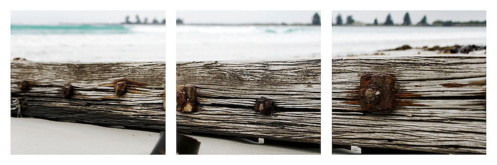 close up of weathered wood and rusted bolts in groyne on Port Fairy beach.