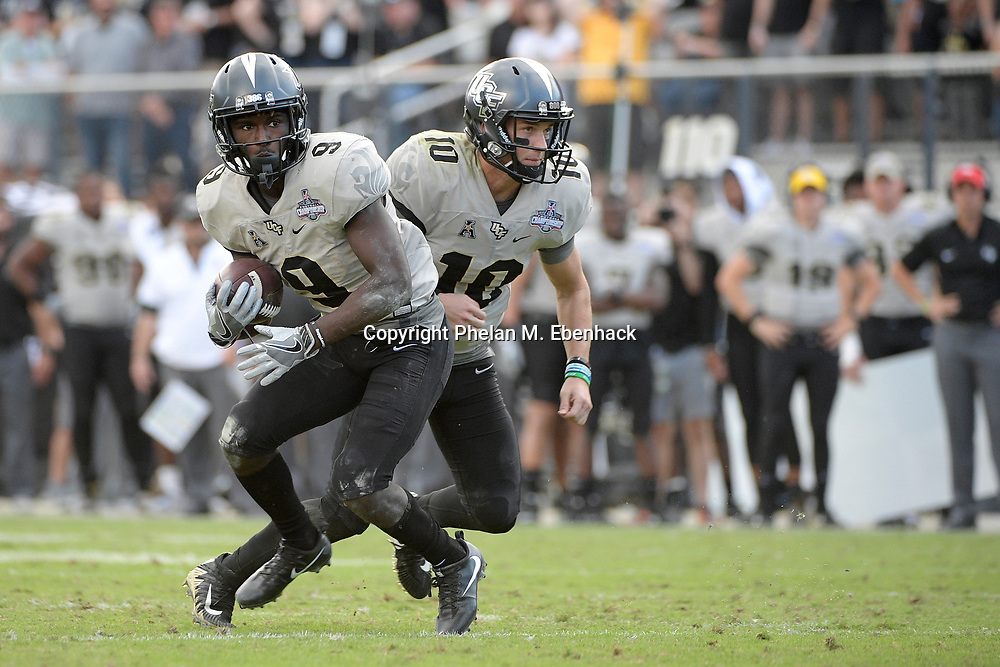 Central Florida running back Adrian Killins Jr. (9) takes a handoff from quarterback McKenzie Milton (10) during the second half of the American Athletic Conference championship NCAA college football game against Memphis Saturday, Dec. 2, 2017, in Orlando, Fla. Central Florida won 62-55. (Photo by Phelan M. Ebenhack)