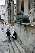 Two men beneath ancient black granite Egyptian Sphinx, Peristyle in Diocletian Palace, Split, Croatia