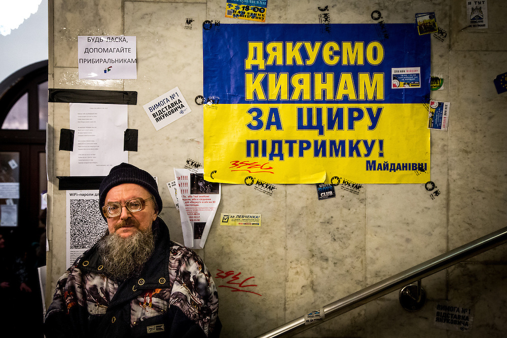 """A man stands in the city hall, next to a blue and yellow poster with the inscription : """"Thank you to the people of Kiev for their support"""""""