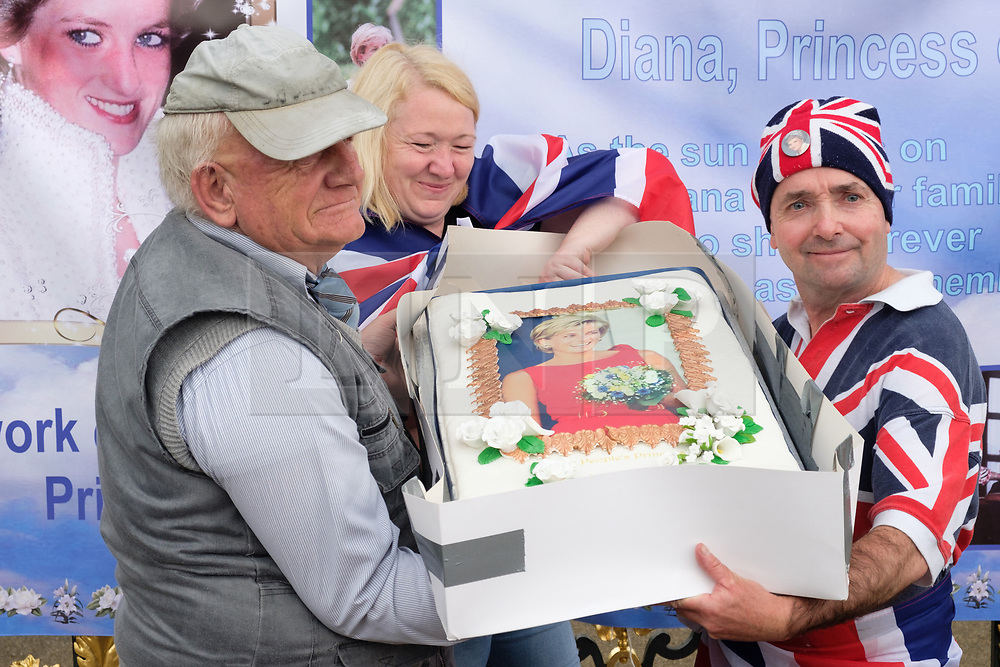 © Licensed to London News Pictures. 29/08/2017. London, UK. British Royal family fans hold a cake featuring the late Princess Diana outside the Golden Gates of Kensington Palace on the eve of the 20th anniversary her death. The Princess died in a car crash in Paris, France, on 31st August 1997. Photo credit: Ray Tang/LNP